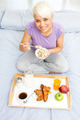Young blonde woman is having breakfast in the bedroom - PhotoDune Item for Sale