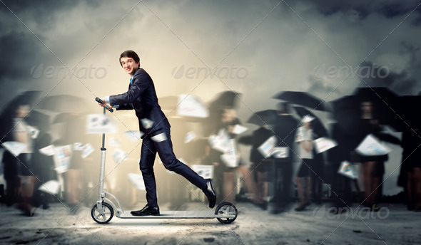 Businessman riding scooter - Stock Photo - Images