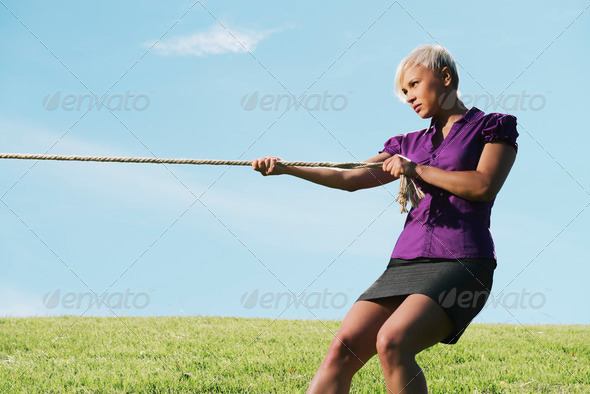 competitive businesswoman playing tug of war with rope - Stock Photo - Images