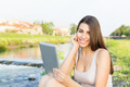 Beautiful young woman sitting by the river using tablet computer - PhotoDune Item for Sale