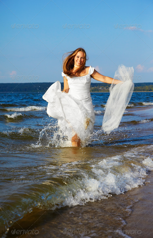 bride running in waves - Stock Photo - Images