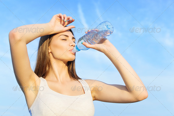 Cute young woman drinking water after workout - Stock Photo - Images