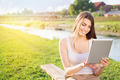 Young student girl sitting by the river using tablet computer - PhotoDune Item for Sale