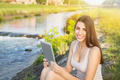 Cute young woman using tablet pc sitting by the river - PhotoDune Item for Sale