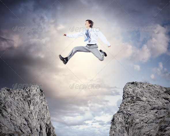 Businessman jumping over gap - Stock Photo - Images