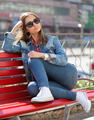girl in jeans sitting on a bench in the street - PhotoDune Item for Sale