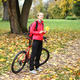 Young girl cyclist with bike enjoy vacation in autumn park - PhotoDune Item for Sale