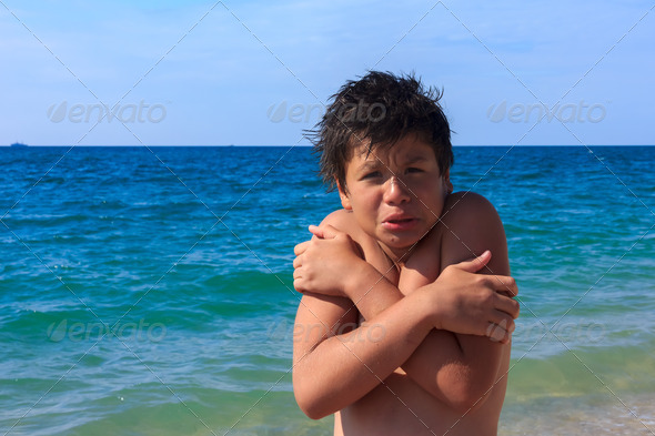 young diver boy freezes on the sea beach - Stock Photo - Images