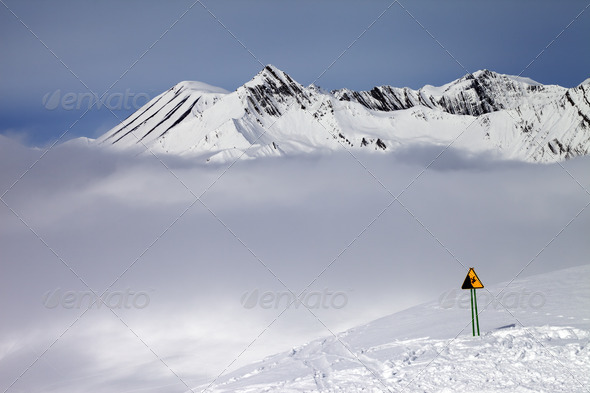 Warning sing on ski slope and mountains in fog - Stock Photo - Images