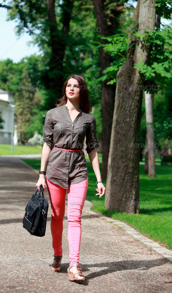 Young Woman with a Computer Bag Walking in a Park - Stock Photo - Images