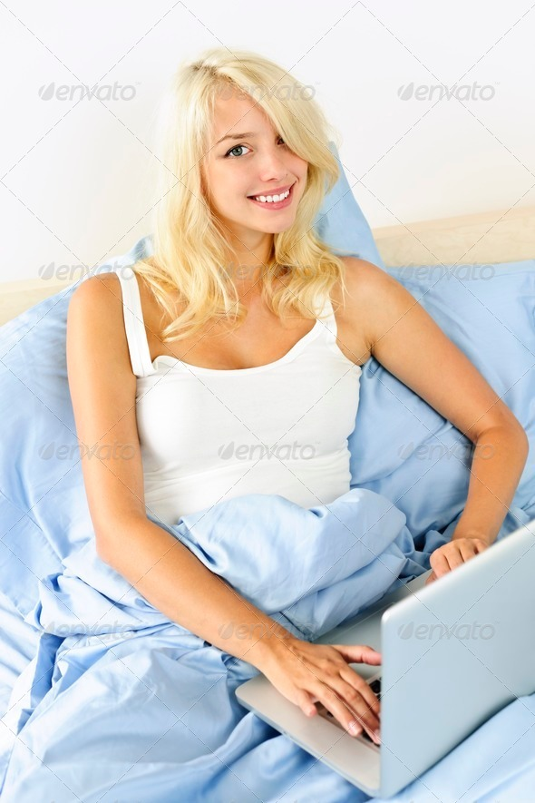 Woman sitting in bed with laptop computer - Stock Photo - Images