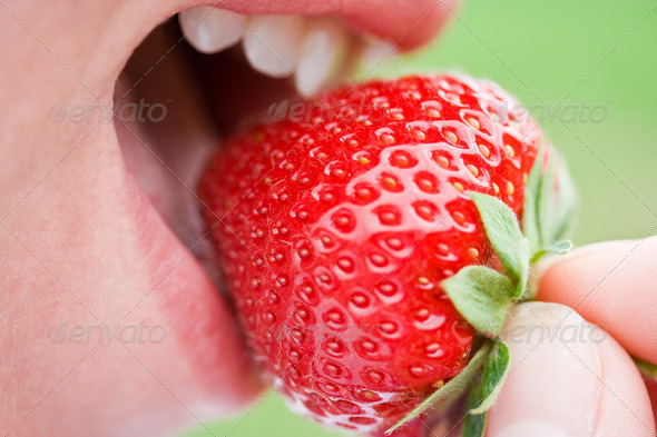 Woman biting strawberry - Stock Photo - Images