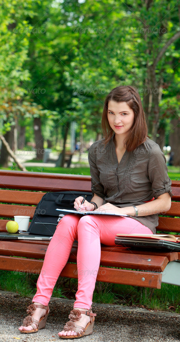 Young Woman Writing Outside in a Park  - Stock Photo - Images