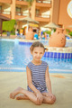 little girl in striped vest near resort's pool - PhotoDune Item for Sale
