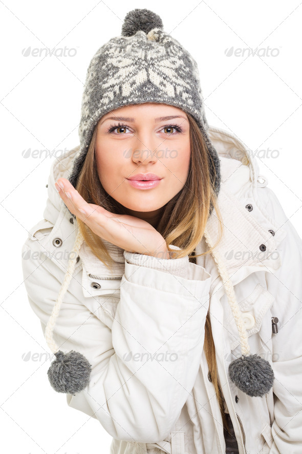 Cute young woman wearing winter hat and jacket blowing kisses - Stock Photo - Images