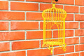 Yellow Birdcage on brick wall background. - PhotoDune Item for Sale