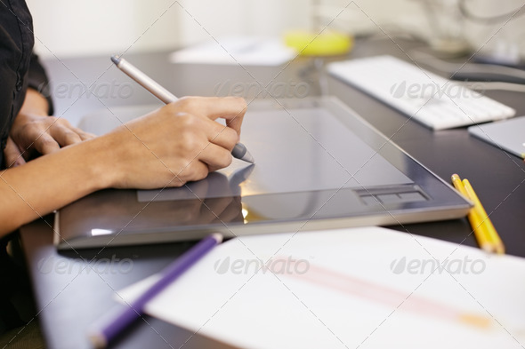 Woman drawing sketches on computer in fashion design studio - Stock Photo - Images
