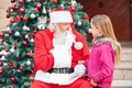 Girl Looking At Santa Claus Gesturing Finger On Lips - PhotoDune Item for Sale