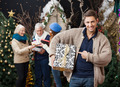 Man Pointing At Christmas Present With Family In Background - PhotoDune Item for Sale