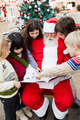 Santa Claus With Children Pointing At Book - PhotoDune Item for Sale