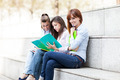 Three female students sitting on a bench with notebooks - PhotoDune Item for Sale