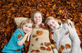 Mom and her daughters lying on a bed of leaves during the fall s - PhotoDune Item for Sale