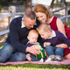 Beautiful Small Young Family Opening Christmas Gifts in the Park. - PhotoDune Item for Sale