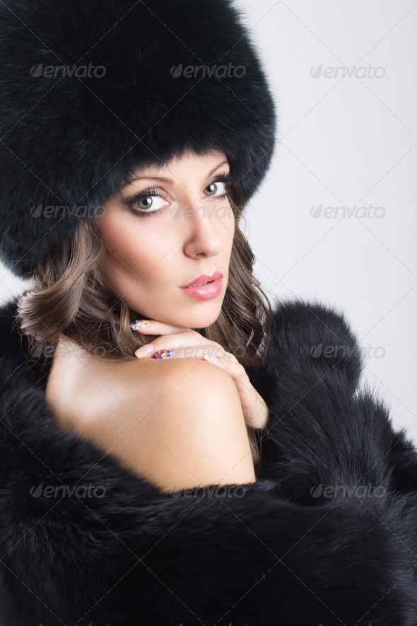 Glamorous young woman wearing black fur coat and hat - Stock Photo - Images