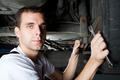 closeup of mechanic working below car with wrench - PhotoDune Item for Sale