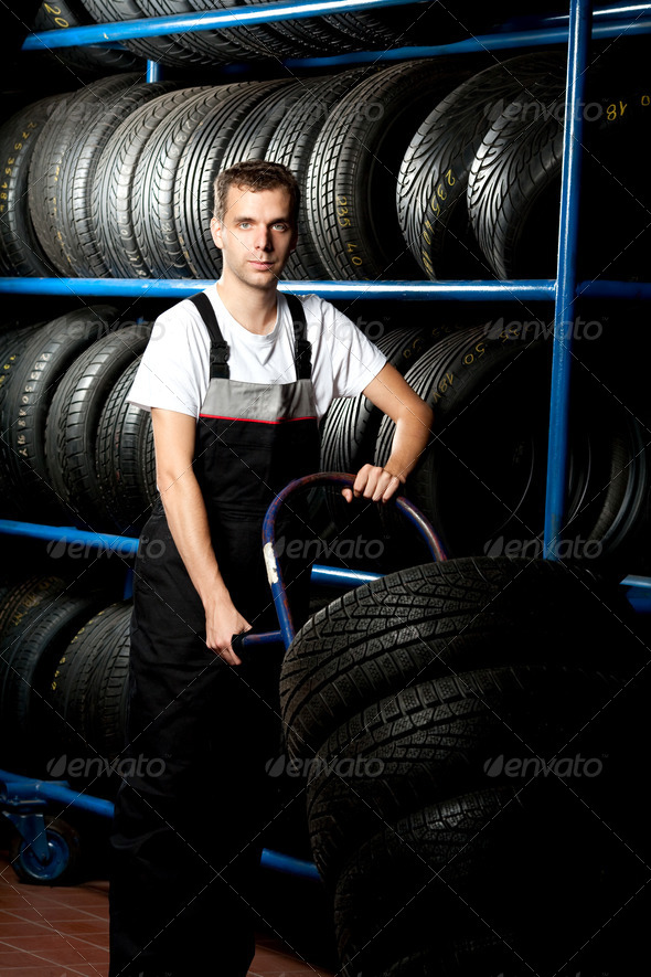 Young mechanic carrying tire in car service - Stock Photo - Images