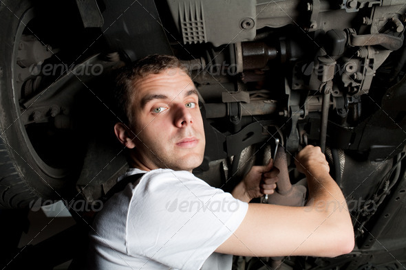 Young Mechanic working below car with wrench - Stock Photo - Images