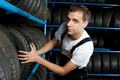 Young mechanic choosing tire in car service - PhotoDune Item for Sale