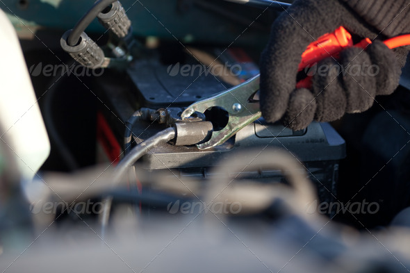 Connecting jumper cable to battery - Stock Photo - Images