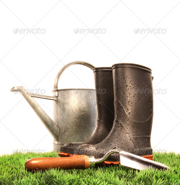 Garden boots with tool and watering can - Stock Photo - Images