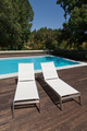 White loungers near a pool with trees in background - PhotoDune Item for Sale