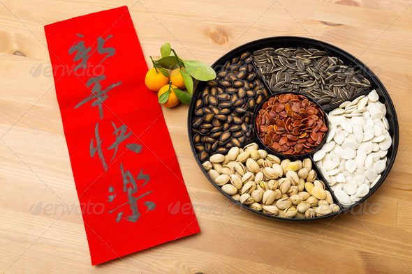 Lunar new year snack tray and chinese calligraphy, meaning is happy new year - Stock Photo - Images
