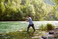 Fisherman standing near river and holding fishing rod - PhotoDune Item for Sale
