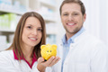 Smiling pharmacist holding up a piggy bank - PhotoDune Item for Sale