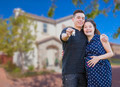 Happy Hispanic Couple In Front of New Home Showing Off Their House Keys. - PhotoDune Item for Sale