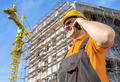 Worker in front of Construction Site talking on smart phone - PhotoDune Item for Sale