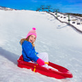 Kid girl playing sled in winter snow - PhotoDune Item for Sale
