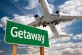 Getaway Green Road Sign and Airplane Above with Dramatic Blue Sky and Clouds. - PhotoDune Item for Sale