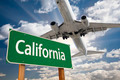 California Green Road Sign and Airplane Above with Dramatic Blue Sky and Clouds. - PhotoDune Item for Sale