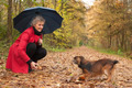 Woman with umbrella playing with her dog - PhotoDune Item for Sale