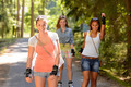 Three women friends roller skating outdoors - PhotoDune Item for Sale