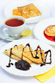 Food of Crepes, cheesecakes with berry sause and cup of tee. - PhotoDune Item for Sale