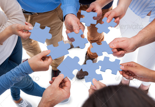 High angle view of people connecting puzzle pieces over white background