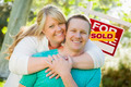 Happy Couple Hug In Front of Sold Real Estate Sign. - PhotoDune Item for Sale
