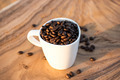 Roasted coffee beans in white cup on wood. - PhotoDune Item for Sale
