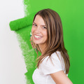 Beautiful happy woman painting a wall - PhotoDune Item for Sale